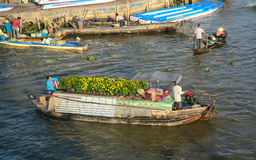 Cargo boats carry flowers at the floating market in Ben Tre, Vietnam Stock Images