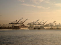 Cargo Boats rest under cranes in Oakland Harbor on a foggy day Stock Photography