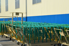 Cargo carts stand near the building of modern plant. Cargo Stock Photo