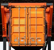 Cargo container. Lifting up orange cargo container in warehouse Stock Photos