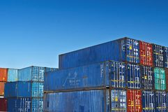 Blue red colored long cargo containers. Cargo containers sit in the portside holding area after offload from a long haul martime transporter. import export royalty free stock photos
