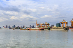 Cargo container ship being towed by the tug of cruising through the city Stock Photography