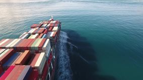 Cargo container ship sails through the sea, ocean waves in open water