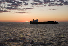 Cargo container ship in sunset. Cargo container ship sailing off into the sunset Royalty Free Stock Photo