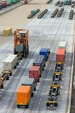 Cargo container shipping terminal. ROTTERDAM, NETHERLANDS - SEP 8, 2013: Straddle carriers moving cargo containers in a shipping terminal in the Port of Royalty Free Stock Photos