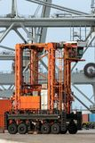 Cargo container shipping terminal. Straddle carrier moving cargo containers in a shipping terminal Royalty Free Stock Images