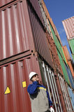 Cargo containers and dock worker. Dock worker talking in phone, large stacks of shipping containers in background Stock Photos