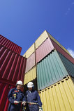 Cargo containers and dock workers. Dock worker talking , large stacks of shipping containers in background, general port activities Royalty Free Stock Photos
