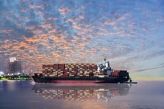 Cargo ship. Cargo containers Ship assist tug boat cargo container harbor on sunset with twilight and clouds background Stock Photos