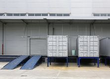 Cargo Containers. Silver Shipping Containers and Ramp in Front of Warehouse Stock Images