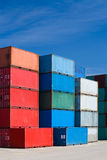 Cargo containers at terminal. Cargo containers - freight stacked at container terminal under blue sky Stock Photos