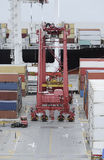Cargo containers truck and a crane in a freight port terminal Stock Photos