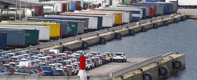 Cargo containers and vehicles in barcelona commercial port wide. Cargo containers and new vehicles waiting to be loaded in a cargo vessel in Barcelona port. The royalty free stock photos