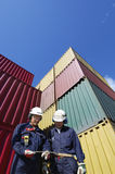 Cargo containers and workers. Port workers with stacks of cargo containers in background stock images
