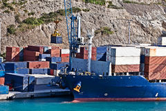 Cargo contgainer ship loading. Crane loading cargo container ship with rock wall in background stock photography