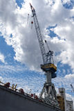 Cargo crane against the blue sky with clouds in the port of Hamb Stock Photo