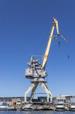 Cargo crane in port. Old cargo crane is in port against blue sky Royalty Free Stock Images