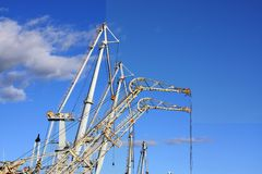 Cargo cranes against cloudy sky. Cargo cranes in industrial port Blue sky background Stock Images