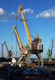 Cargo cranes closeup. Marine cranes in the port closeup to the background of blue sky with clouds stock image