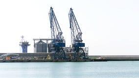 Cargo cranes and grain dryers. In Balchik harbor Royalty Free Stock Image