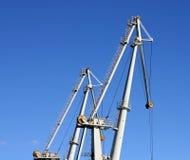 Cargo cranes in harbour. Cargo cranes in industrial port. Clear blue sky background Stock Photos
