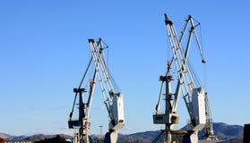 Cargo cranes ship and shore. Cargo cranes of ship crossed with dock cranes.nBlue sky background Stock Photos