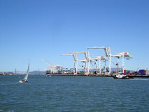 Cargo Cranes, tugboat and sail boat in Oakland Harbor on a nice Stock Images