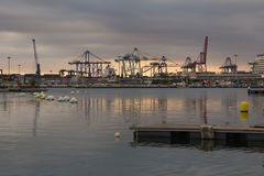 Cargo cranes working at port, behind the sunlight between the clouds Royalty Free Stock Images