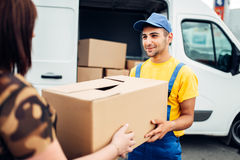 Cargo delivery, courier gives parcel to the client. Cargo delivery service, male courier in uniform gives a parcel to the client, distribution business. Truck Royalty Free Stock Photography