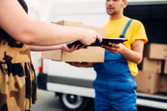 Cargo delivery, courier gives parcel to the client. Cargo delivery service, male courier in uniform gives a parcel to the client, distribution business. Truck Royalty Free Stock Images