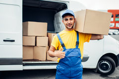 Cargo delivery service, male worker thumb up. Cargo delivery industry, male worker in uniform shows thumb up. Empty container Stock Photography