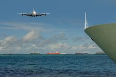 Cargo, depaturing & arriving. Ships, plane. There are landing big, modern cargo jet-plane above sea and departuring loaded colorful vessels on horizon. The bow Stock Image
