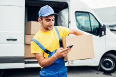 Cargo distribution industry, delivery service. Worker in uniform with box and mobile phone in hands. Empty container royalty free stock photos
