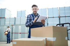 Cargo distribution worker checking boxes. Content confident handsome male cargo distribution worker checking boxes and making notes in document while standing at stock photos