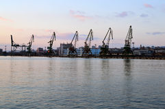 Cargo docks with dark cranes' silhouettes after sunset, Varna Port, Bulgaria Stock Images