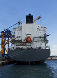 Cargo en mer avec le petit bateau orange Image libre de droits