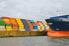 Cargo freight containers. Stacked at harbor terminal with big containership Stock Photos
