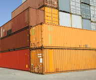 Cargo freight containers at harbor terminal. Cargo shipping containers stacked at harbor freight terminal under clear blue sky royalty free stock images