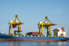 Cargo freight ship container with working crane Royalty Free Stock Images
