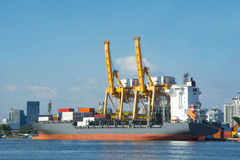 Cargo freight ship container with working crane Stock Photo