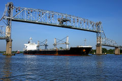 Cargo Freight Ship Sailing under Lift Span Bridge. Loaded seafaring freight carrier cargo ship and following tugboat sailing an American river commercial stock images