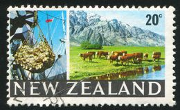 Cargo hoist. NEW ZEALAND - CIRCA 1968: stamp printed by New Zealand, shows cargo hoist, grazing cattle,  circa 1968 stock image