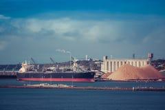 Cargo industriel dans le port avec des grues sous des nuages Photos libres de droits