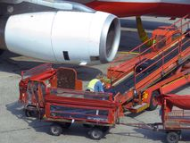 Cargo load. Worker loading baggage in an airplane royalty free stock image