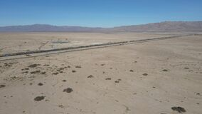 Cargo locomotive railroad engine crossing Arizona desert wilderness.