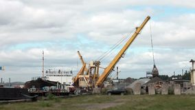 Cargo mooring. Unloading of a cargo vessel in the river port stock video