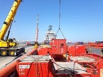 Cargo operations ongoing onboard supply vessel working for oil and gas industry. A shore crane is lifting a container royalty free stock photography