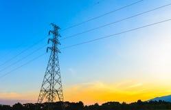 Cargo, pilões da eletricidade e linhas de alta tensão no por do sol Imagens de Stock Royalty Free