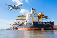 Cargo plane flying above ship port for logistic import export Royalty Free Stock Image