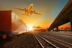 Cargo plane flying over container trains and commercial shipyard background royalty free stock image